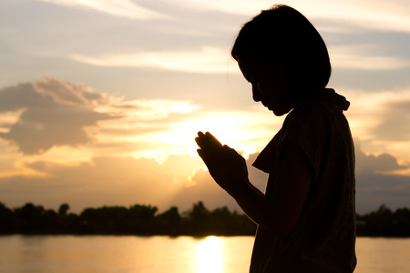protection of the bible: Silhouette of woman praying over beautiful sunset background. Stock Photo
