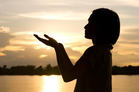 Silhouette of woman praying over beautiful sunset background. Standard-Bild