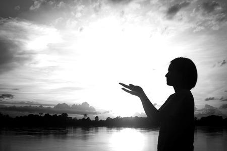 female hands: silhouettes Women praying hand over beautiful sun set background.
