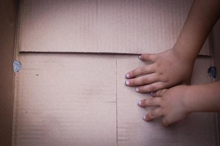 niños pobres: Caja de papel con las manos los niños pobres.