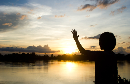 silhouettes Women show her hand over beautiful sun set background.Bye Bye hand sign.
