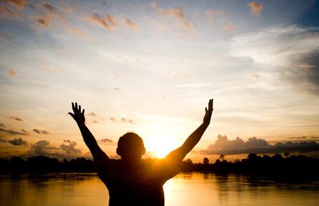 orando: Siluetas hombre rezando mano sobre hermoso fondo puesta de sol.