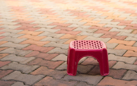 out door: Small red chair on out door floor.