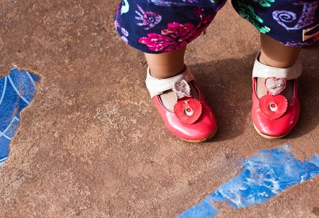 out door: Closeup of cute Red shoes with a little girl standing on out door hard floor.Focused on red shoes.