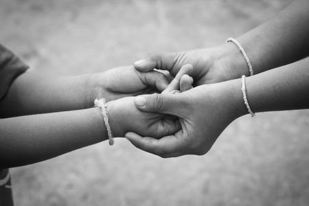 caja fuerte: Niños pobres que sostiene un pequeño muchacho manos. Foto de archivo