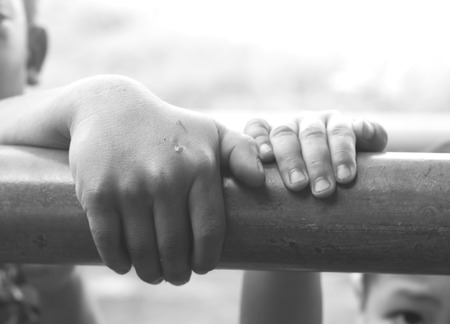 poor children: Poor Children use hand pull fence. Stock Photo