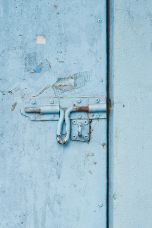 Old metal door with chipped blue paint and rusted lock.