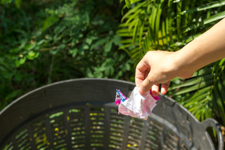 scrunched: Closeup cropped portrait of someone tossing crumpled piece of ice-cream plastic package in trash can, isolated outdoors green trees background Stock Photo