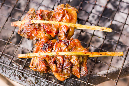 thai: Chickens grilled on iron stove, fireplace, Traditional Thai style grilled chicken stick.