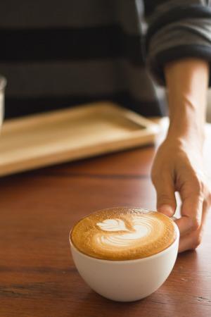 20 29 years: Waiter serving coffee on poor lighting.Focused at coffee cup.