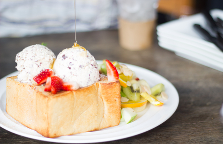 lambent: selective focus of honey toast  with fruit and icecream on poor lighting. Stock Photo