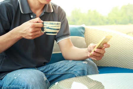 enjoyment: Asian man is holding a cup of hot coffee and use his mobile phone.Focused at coffee cup.