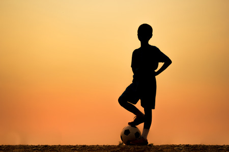 boys playing: Silhouettes of Asian boy is playing soccer.
