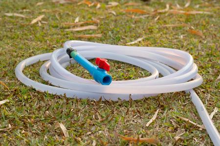 feild: plastic hose with plastic pipe valve on grass feild.