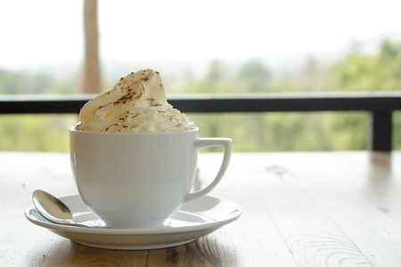 Close up of whipped cream topped with chocolate on hot cocoa drink.