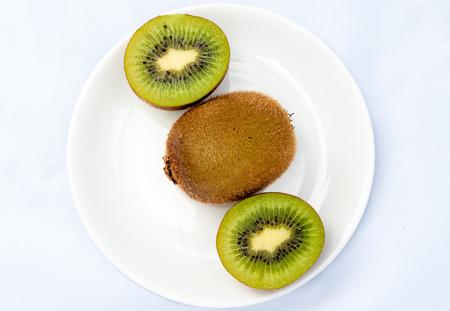 kiwis: kiwis on plate  with white background Stock Photo