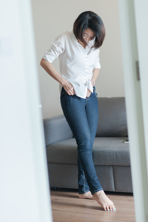 weight room: BW  Woman trying on jeans and smiling tight Stock Photo