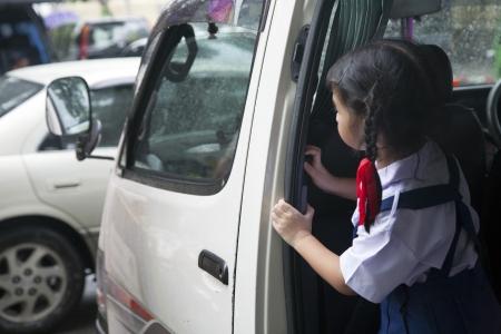 Little school girl waiting for her friends on school van