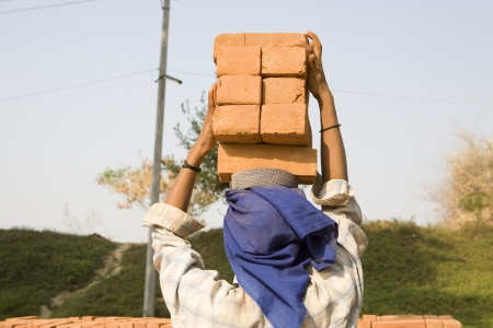 Female worker carry brick on her head,Myanmar Stock Photo