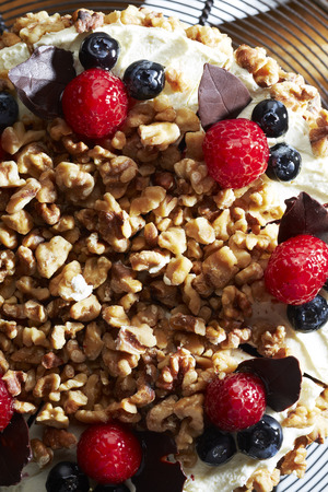 Walnuts and berries decoration on cake,close up photo
