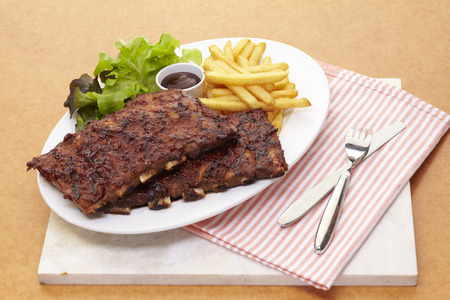 Barbecue pork ribs serve with french fried and salad photo