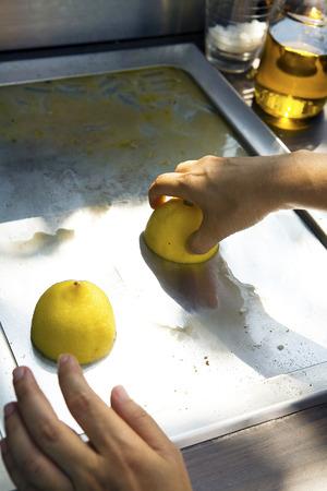 lemon water: Hand using lemon to clean top of electric pan
