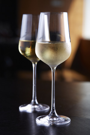 white wine glass: Glasses of white wine on table