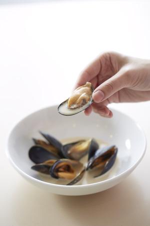 petoncle: Une main tenant coquille Saint-Jacques avec de la viande de p�toncle et de la soupe � l'int�rieur