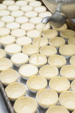 egg tart: Pot filling egg pudding into puff of egg tart Stock Photo