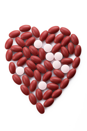 antibiotic pink pill: Red and pink colour pills group in heart shape Stock Photo