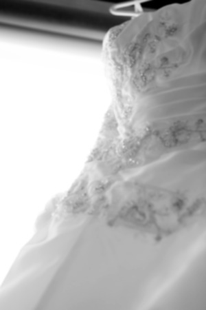 close out: Close up of Wedding dress hanging near window out of focus,blur background,black and white Stock Photo