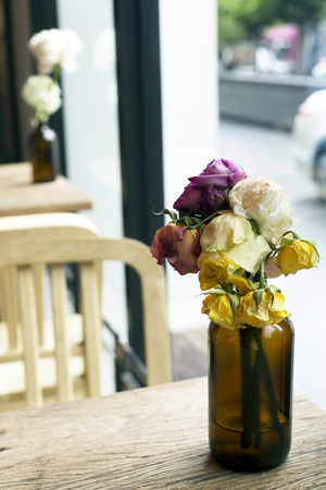 wither: Wither roses in bottle on wooden table