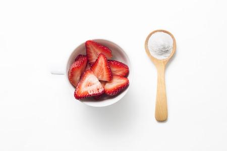 gaseosas: Fresas y bicarbonato de sodio en una cuchara de madera para blanquear los dientes Foto de archivo
