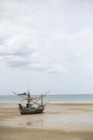 monsoon clouds: Small fishing boat stay on beach in monsoon season Stock Photo