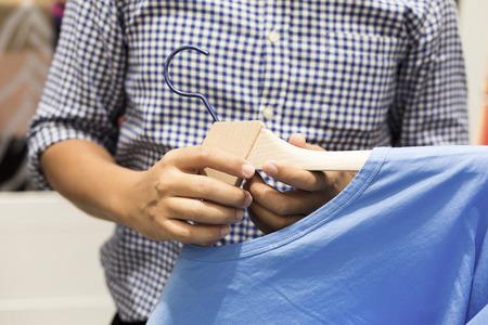 clotheshanger: Hand holding hunger of T-shirt on shopping Stock Photo