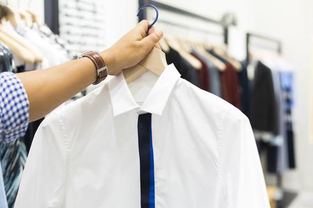 clotheshanger: Hand holding hunger of shirt on shopping Stock Photo
