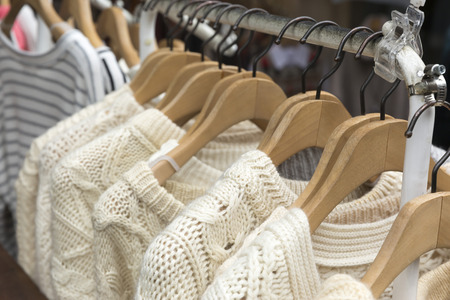 Beige color knitting sweater on clothes rack Фото со стока