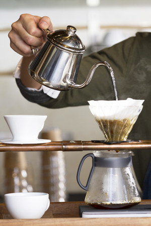 hand holding pot pouring hot water to dripping coffee