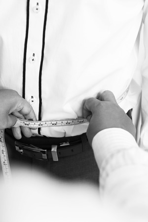 customer tailor: Hand of Man tailor making waist measurement for customer Stock Photo