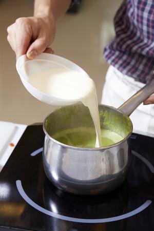Hand adding milk cream into pot of pea soup
