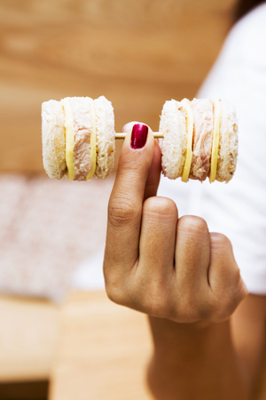 weight control: Weight control concept-Hand lifting mini sandwiches in dumbbell shape