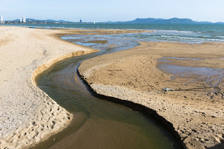 wind down: Small canal on sand beach bring water to the sea