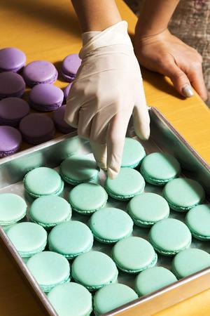 paletas de caramelo: Mano preparando macarrones en la bandeja