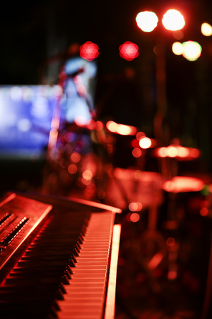 Piano synthesiser on stage with red lighting Stock Photo