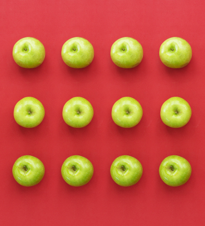 Green fresh apples on red paper background Stock Photo