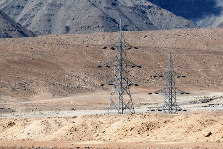 High Voltage Poles or Electric tower is transmission high voltage power on the snow mountain valley at Leh Ladakh , Jammu and Kashmir , India - Technology infrastructure scene Banco de Imagens