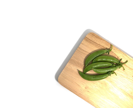 Peas on a cutting board on a white background. Stock Photo
