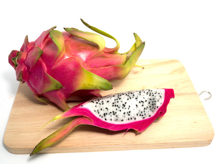 Dragon fruit on a cutting board on a white background.
