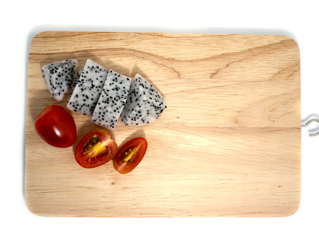Dragon fruit and cherry tomatoes on a cutting board on a white background.