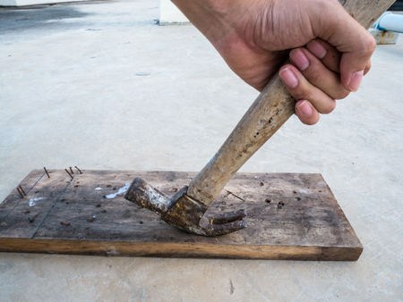 Remove the tack from the wooden plate with a hammer. Stock Photo